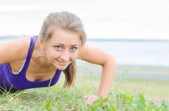 Pretty woman doing push-ups. Stock Photo