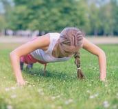 Pretty woman doing push-ups. Stock Photos