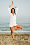 Pretty woman doing yoga on the beach Stock Photos