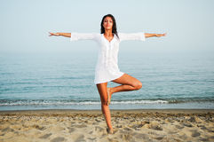 Pretty woman doing yoga on the beach Stock Photography