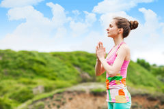 Pretty woman doing yoga exercises on nature landscape Royalty Free Stock Images