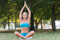 Pretty woman doing yoga exercises in the park Stock Image