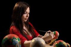 Pretty woman drawing patterns on matrioshka Royalty Free Stock Images