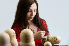 Pretty woman drawing patterns on matrioshka Royalty Free Stock Photography