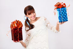 Pretty woman in dress compares  boxes with gifts Stock Photos