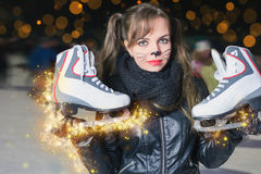 Pretty woman dressed in cat fancy dress holding skates shoes Stock Image