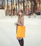 Pretty woman dressed a coat and fur hat walking outdoors. With shopping bag in the city Stock Photo