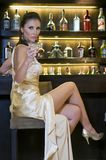 Pretty woman drinking in a bar Stock Images