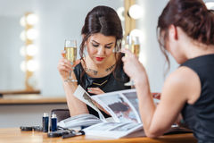 Pretty woman drinking champagne and reading magazine in dressing room. Pretty young woman drinking champagne and reading magazine near the mirror in dressing Royalty Free Stock Photos