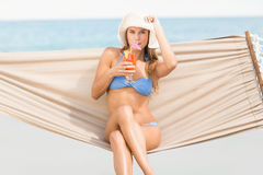 Pretty woman drinking cocktail in the hammock Royalty Free Stock Image
