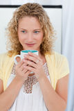 Pretty woman drinking coffe in her kitchen Royalty Free Stock Images