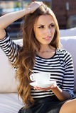 Pretty woman drinking coffee in a cafe outdoors Stock Images