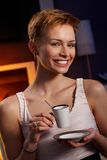 Pretty woman drinking coffee in cosy room. Smiling happy royalty free stock photography