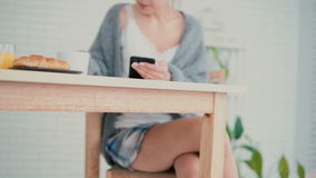 Pretty woman drinking coffee in pajamas at breakfast and using smartphone technology in kitchen at home. Brunette girl sitting at the table and surfs the stock footage