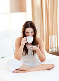 Pretty woman drinking coffee sitting on bed Royalty Free Stock Image