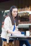 Pretty woman drinking coffee in the street stock photography