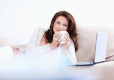 Pretty woman drinking coffee and using a laptop Royalty Free Stock Photo
