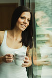 Pretty woman drinking a cup of cofee next the window Royalty Free Stock Photo