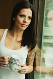 Pretty woman drinking a cup of cofee next the window Stock Photography