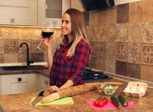 Pretty woman drinking some wine at home in kitchen. The girl is going to cook dinner, resting Royalty Free Stock Images