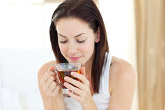 Pretty woman drinking tea. Sitting on her bed Stock Photos