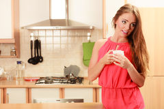 Pretty woman drinking tea or coffee at home. Gorgeous young girl with hot beverage relaxing in kitchen Royalty Free Stock Images