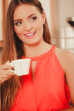 Pretty woman drinking tea or coffee at home. Gorgeous young girl with hot beverage relaxing in kitchen Royalty Free Stock Image
