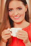 Pretty woman drinking tea or coffee at home. Gorgeous young girl with hot beverage relaxing in kitchen Royalty Free Stock Photo