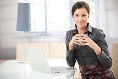 Pretty woman drinking tea at home using laptop Royalty Free Stock Images