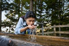 Pretty woman drinking water. Beautiful young woman drinking water from a well in the middle of a forest stock images