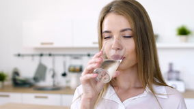 Pretty woman drinks water from a glass cup in the morning. Young cute girl drink net water from glass cup. Sip of purity of skin. Sunny portrait of 20s lady with stock video