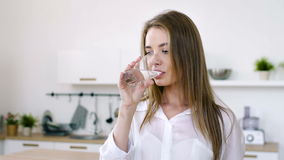 Pretty woman drinks water from a glass cup in the morning. Young cute girl drinking net water from glass cup indoors. Sip of purity of skin. Day portrait of 20s stock footage