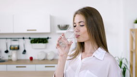 Pretty woman drinks water from a glass cup in the morning. Young cute girl drinking net water from glass cup indoors. Sip of purity of skin and natural stock video footage