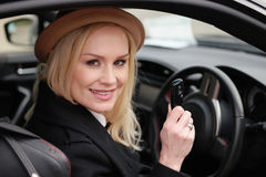 Pretty woman driver holding her car key in the car. Pretty woman driver holding her car key as she sits behind the steering wheel in the car smiling happily at Stock Images