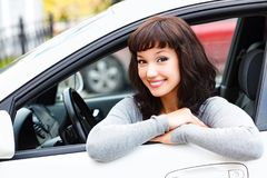 Pretty woman driver smiling to you. From the white car Royalty Free Stock Photo