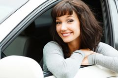 Pretty woman driver smiling to you. From the white car Stock Images