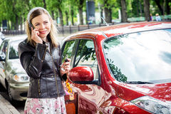 Pretty woman driver. Young woman holding keys to new car and smiling Royalty Free Stock Photo