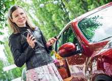 Pretty woman driver. Young woman holding keys to new car and smiling Royalty Free Stock Photos