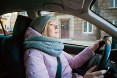 Pretty woman driving car on a cold autumn or winter day stock photography
