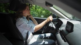 Pretty woman driving modern car along country road. Fastened with safety belt attractive female in casual clothing confidently driving car on background of green stock video