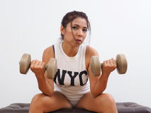 Pretty woman with a dumbbell in each hand Stock Images