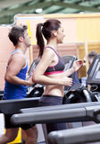 Pretty woman with earphones using a treadmill Royalty Free Stock Image