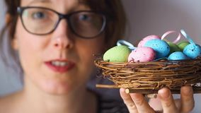 Pretty woman with Easter eggs in nest. Greetings