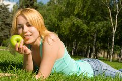 Pretty woman eating apple on the summer glade Royalty Free Stock Photos