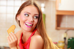 Pretty woman eating biting gingerbread cookie. Royalty Free Stock Photos