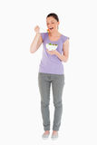 Pretty woman eating a bowl of salad while standing Stock Images