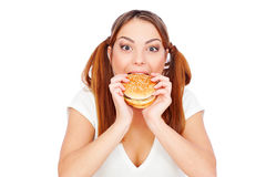 Pretty woman eating burger with gusto Royalty Free Stock Image