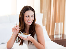 Pretty woman eating cereals sitting on bed. At home Royalty Free Stock Images