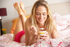 Pretty Woman Eating Dessert In Bed Stock Photos