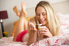 Pretty Woman Eating Dessert In Bed Stock Images